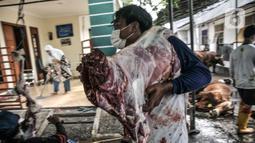 Panitia memindahkan daging hewan kurban saat perayaan Hari Raya Idul Adha 1442 H di Musala Nurul Huda, Jakarta, Selasa (20/7/2021). Di tengah pandemi COVID-19, warga di sejumlah wilayah Ibu Kota tetap menggelar penyembelihan hewan kurban meski secara terbatas. (merdeka.com/Iqbal S. Nugroho)
