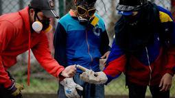 Tiga mahsiswa menyalakan petasan selama bentrokan dengan pasukan keamanan selama protes menuntut peningkatan anggaran beasiswa dan membuka kembali kafetaria universitas di Caracas, Venezuela (21/11). (AP Photo/Ariana Cubillos)