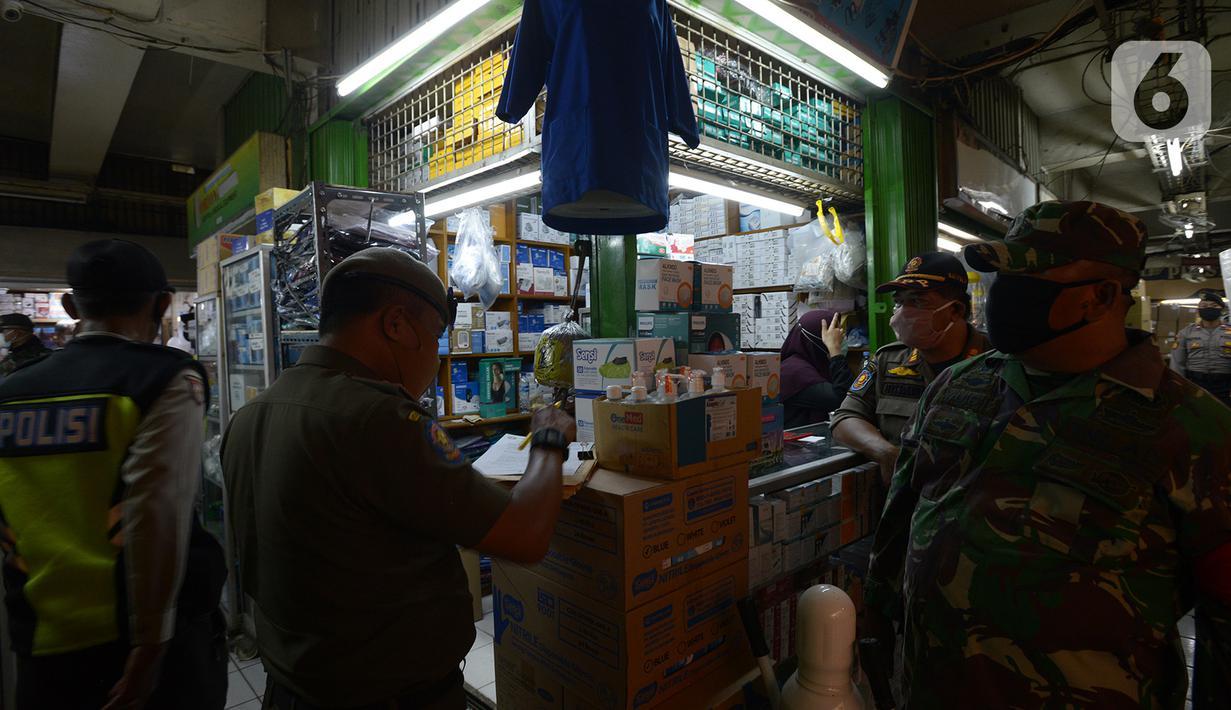 Petugas gabungan melakukan razia pertokoan dan tempat makan di Pasar Pramuka, Jakarta, Kamis (24/9/2020). Upaya mencegah penularan virus corona terus dilakukan dengan merazia penggunaan masker dan tempat usaha makan yang masih melayani makan di tempat. (merdeka.com/Imam Buhori)