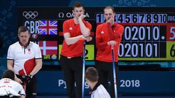 Atlet Curling dari Inggris Thomas Muirhead dan Kyle Smith menunggu giliran saat sesi round robin antara Inggris dan Denmark selama Olimpiade Musim Dingin Pyeongchang 2018 di Gangneung Curling Centre di Gangneung (19/2). (AFP Photo/Wang Zhao)