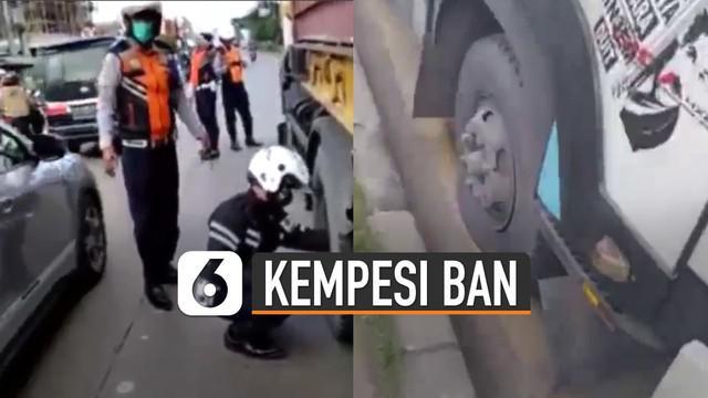 Terlihat seorang petugas Dishub didampingi rekannya sedang melakukan aksinya ngempesin dua ban depan truk.