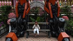 Seorang anak berpose di bawah patung logam 'Transformers' di kuil Buddha Wat Tha Kien di Nonthaburi, Thailand (18/6). Kuil ini tengah berjuang untuk tetap relevan di era modern dengan meletakkan patung logam Transformers. (AFP Photo/Lillian Suwanrumpha)