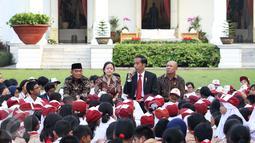 Presiden Joko Widodo saat mendongeng didepan puluhan pelajar di halaman tengah Istana, Jakarta, Rabu (17/5). Kegiatan mendongeng ini untuk memperingati hari buku nasional. (Liputan6.com/Angga Yuniar)