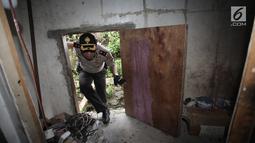 Petugas polisi memeriksa sudut rumah lokasi penggerebekan peredaran narkoba di Kampung Ambon, Jakarta, Rabu (24/1). Satu pelaku lainnya berhasil melarikan diri saat dilakukan penggerebekan dan dalam pengejaran polisi. (Liputan6.com/Arya Manggala)