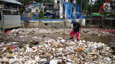 Petugas membersihkan sampah yang menyumbat Pintu Air Manggarai, Jakarta, Selasa (26/2). Meningkatnya debit air Sungai Ciliwung menyebabkan terjadi penumpukan sampah di Pintu Air Manggarai. (Liputan6.com/Faizal Fanani)