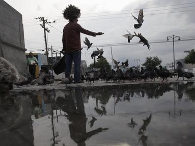 Jesus Moreno saat memberikan makanan ke merpati liar di pusat kota Monterrey, Meksiko, Selasa (7/7/2015). Bagi Moreno, merpati melambangkan sebuah perdamaian dan memberi makan mereka adalah cara untuk berkomunikasi dengan Tuhan. (REUTERS/Daniel Becerril)