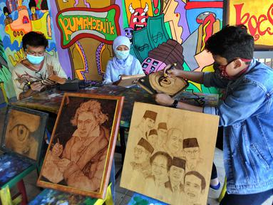 Arfan (55) seniman pelukis bakar atau pyrography bersama anak dan istri menyelesaikan karya seni lukis bakar di atas media kayu dan kulit  di galeri Rumah Oenik, Kampung Ragamukti, Tajur Halang, Bogor, Senin (28/9/2020). (Merdeka.com/Arie Basuki)