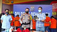 Kepala Polresta Pekanbaru (tengah) memperlihatkan barang bukti penyerangan petugas Bea Cukai Riau. (Liputan6.com/M Syukur)