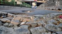 Tampak jalan Galunggung yang rusak dan berlubang di Setia Budi, Jakarta, Selasa (30/7/2019). Minimnya pengawasan serta perawatan jalan oleh pihak terkait dapat mengakibatkan kecelakaan dan rusaknya bus Transjakarta. (merdeka.com/Iqbal S Nugroho)