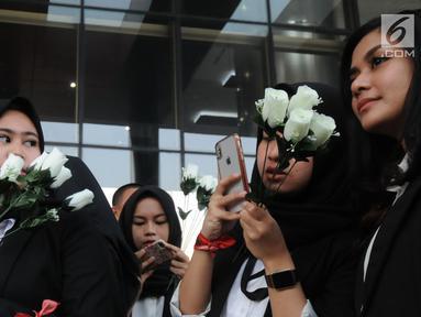 Sejumlah wanita membawa bunga mawar menyambut kedatangan penyidik senior KPK, Novel Baswedan saat masuk kerja kembali di gedung KPK, Jakarta, Jumat (27/7). Novel absen 16 bulan lantaran berobat matanya setelah diserang air keras. (Merdeka.com/Dwi Narwoko)