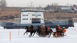 Peserta memacu troika selama bersaing dalam balapan kuda Ice Derby di Sungai Yenisei yang membeku, Krasnoyarsk, Rusia, Sabtu (16/3). Kejuaraan balap kuda ini arenanya berada di atas sungai yang membeku. (Reuters/Ilya Naymushin)