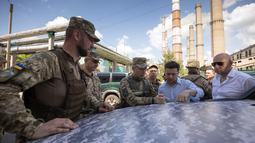 Presiden Ukraina, Volodymyr Zelensky berbincang dengan prajurit saat mengunjungi garis depan medan pertempuran dengan separatis pro-Rusia di Lugansk, Senin (27/5/2019). Zelensky berada pada jarak sekitar 400 meter dari lokasi para pemberontak. (STR/UKRAINE PRESIDENTIAL PRESS SERVICE/AFP)