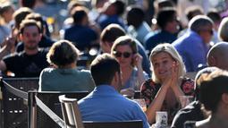 Orang-orang bersosialisasi di bawah sinar matahari di meja luar di Soho, London, ketika pemerintah Inggris mempertimbangkan pembatasan baru pada Minggu (20/9/2020). Inggris kemungkinan akan kembali memberlakukan tindakan lockdown akibat lonjakan tajam infeksi corona COVID-19 (DANIEL LEAL-OLIVAS/AFP)