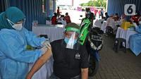 Vaksinator menyuntikkan vaksin COVID-19 secara drive-thru kepada warga lanjut usia di area parkir Hall C JIExpo Kemayoran, Jakarta, Rabu (3/3/2021). Pelaksanaan vaksinasi drive thru bertujuan meningkatkan partisipasi masyarakat terutama Lansia untuk divaksin covid-19. (Liputan6.com/Herman Zakharia)