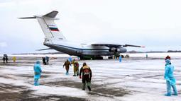 Petugas medis menyambut kedatangan warga yang turun dari pesawat militer di sebuah bandara luar Tyumen, Rusia, Rabu (5/2/2020). Seluruh warga yang dievakuasi dari Wuhan menyusul wabah virus corona tersebut akan dikarantina selama dua minggu di Siberia. (AP Photo/Maxim Slutsky)