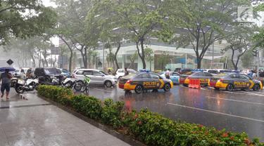 Sejumlah mobil petugas kepolisian saat menutup akses menuju Bursa Efek Indonesia, Jakarta, Senin (15/1). Balkon lantai 1 tower II Bursa Efek Indonesia (BEI) ambruk pada Senin (15/1/2018). (Liputan6.com/Herman Zakharia)
