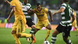 Bek Juventus, Alex Sandro, berusaha melewati kepungan pemain Sporting CP pada laga Liga Champions di Stadion Jose Alvalade, Lisbon, Selasa (31/10/2017). Kedua klub bermain imbang 1-1. (AFP/Patricia De Melo Moreira)