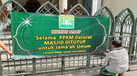 Seorang pengurus Masjid Jami Kota Malang memasang informasi tentang penutupan masjid untuk jamaah umum termasuk tak menggelar malam takbiran dan salat idul adha di masa PPKM Darurat.  (Dok Masjid Jami Malang)