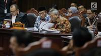 Ekspresi Ketua KPU Arief Budiman (kanan) saat mengikuti sidang sengketa Pilpres 2019 di Gedung MK, Jakarta, Selasa (18/6/2019). Sidang tersebut beragendakan mendengarkan jawaban dari termohon. (Liputan6.com/Faizal Fanani)