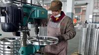 Seorang pekerja wanita membuat lubang baut pada pelek di pabrik pembuatan pelek sepeda motor di Jinhua, Provinsi Zhejiang, China (14/1). (AFP Photo/China Out)