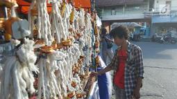 Pedagang merapikan pelita dagangannya yang dijual di Jalan Sam Ratulangi, Kota Gorontalo, Rabu (22/5/2019). Pelita yang terbuat dari botol bekas tersebut dijual dengan harga Rp 5 ribu hingga Rp 12 ribu per buah. (Liputan6.com/Arfandi Ibrahim)
