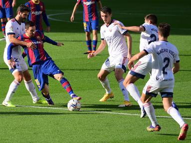 Bek Osasuna, Raul Navas (kiri) berebut bola dengan penyerang Barcelona, Lionel Messi pada pekan ke-11 Liga Spanyol 2020-2021di stadion Camp Nou, Minggu (29/11/2020). Barcelona berhasil pesta gol 4-0 saat menjamu Osasuna. (LLUIS GENE / AFP)