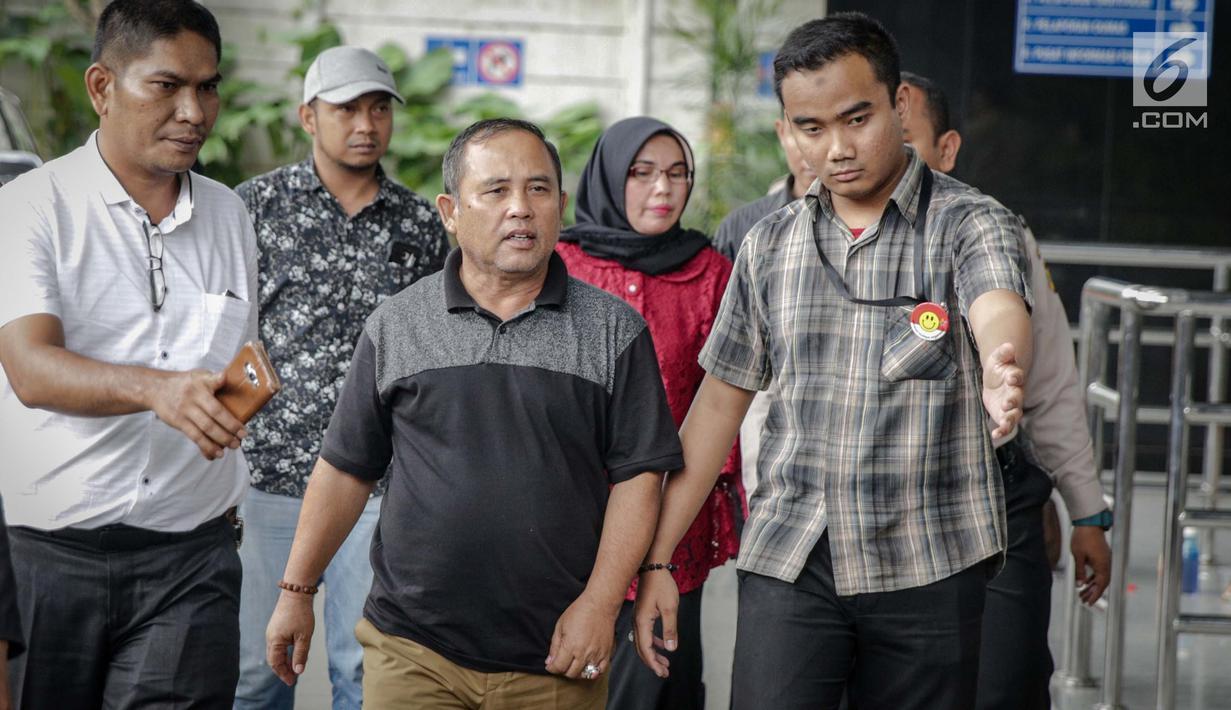 Asisten III Pemprov Jambi Syaifuddin (tengah), Anggota DPRD Jambi Nurhayati (belakang) dikawal petugas memasuki Gedung KPK, Jakarta, Rabu (29/11). KPK melakukan operasi tangkap tangan di Provinsi Jambi. (Liputan6.com/Faizal Fanani)
