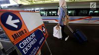 Penumpang membawa barang bawaannya usai menaiki kereta di Stasiun Gambir, Jakarta, Rabu (29/11). (Liputan6.com/JohanTallo)