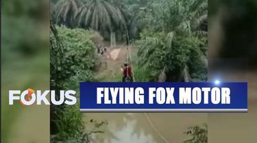 Dua orang wanita muda menyebrangi sungai menggunakan sepeda motor yang tergantung tali layaknya flying fox.