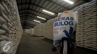 Pekerja memanggul karung Beras milik Badan Urusan Logistik (Bulog) di Gudang Bulog kawasan Kelapa Gading, Jakarta Utara, Selasa (7/6). Bulog memiliki stok beras sebanyak 2,1 juta ton. (Liputan6.com/Johan Tallo)