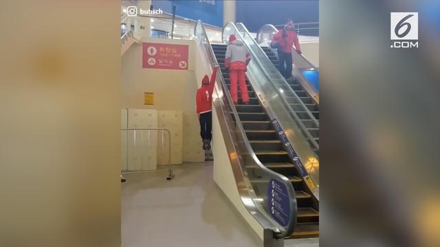 Ada-ada saja yang dilakukan pria ini untuk melewati eskalator, yaitu dengan bergelantungan.