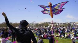 Seorang pria menerbangkan layang-layang pada Festival Blossom Kite di dekat Monumen Washington di Washington, D.C., Amerika Serikat, Sabtu (31/3). Festival ini merupakan serangkaian kegiatan menyambut bunga sakura bermekaran. (Eva HAMBACH/AFP)