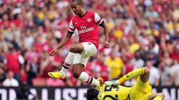 Striker Arsenal Theo Walcott (kiri) melompat menghindari benturan dengan kiper Tottenham Hotspur Hugo Lloris (kanan) pada pertandingan sepak bola Liga Utama Inggris antara Arsenal dan Tottenham Hotspur di Stadion Emirates di London (01/09/2013). (AFP/Glyn