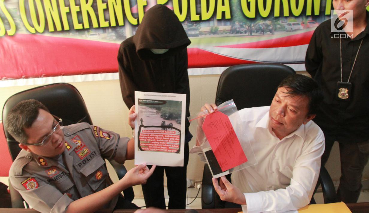 Petugas menunjukkan barang bukti beserta pria IB alias Ismail di Polda Gorontalo, Selasa (28/5/2019). IB harus berurusan dengan pihak kepolisian setelah ia memposting salah satu video kekerasan yang sudah ditambah bahwa itu merupakan kekerasan yang dilakukan Kepolisian.(Liputan6.com/Arfandi Ibrahim)