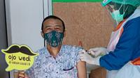 Hendry Ego, mantan Ketua Umum Persikmania saat menjalani vaksinasi COVID-19 di Kantor Disbudparpora Kota Kediri. (Bola.com/Gatot Susetyo)