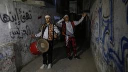 "Dua pemuda ""Musharati"" Palestina memukul gendang saat membangunkan umat muslim untuk sahur pada malam kedua selama bulan suci Ramadan di Rafah di Jalur Gaza selatan (25/4/2020). (AFP/Said Khatib)"