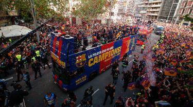 Para pemain Barcelona berada di atas bus saat melakukan parade di Barcelona (30/4). Parade ini untuk merayakan juara La Liga Spanyol yang berhasil diraih oleh tim sepak bola Barcelona. (AP/Manu Fernandez)