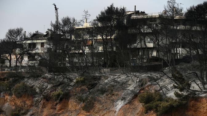 Sejumlah pohon dekat pantai terbakar usai kebakaran hebat melanda Desa Mati, timur Athena, Selasa (24/7). Polisi dan petugas penyelamat masih bertugas di lokasi kebakaran untuk mencari para korban. (AP Photo/Thanassis Stavrakis)