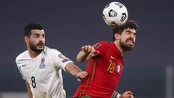 Pemain Portugal, Pedro Neto, duel udara dengan pemain Azerbaijan, Coshqun Diniyev, pada laga kualifikasi Piala Dunia 2022 di Stadion Juventus, Turin, Kamis (25/3/2021). Portugal menang dengan skor 1-0. (Fabio Ferrari/LaPresse via AP)