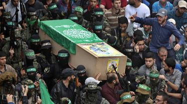 Tentara Hamas mengenakan topeng dan membawa senjata mengiringi peti jenazah enam pejuang mereka yang tewas di Deir el-Balah, Jalur Gaza (6/5). Sebelumnya telah terjadi ledakan yang menewaskan enam pejuang Hamas pada Sabtu (5/5). (AP/Khalil Hamra)