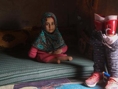 Bocah Suriah, Maya Merhi berpose dekat kaki prostetiknya yang dihiasi bendera Turki di kamp Serjilla, 9 Desember 2018. Sebelumnya, gadis 8 tahun yang lahir tanpa kaki karena kondisi bawaan terpaksa menggunakan kaki palsu dari kaleng. (Aaref WATAD/AFP)