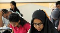 Peserta melihat soal SBMPTN 2018 di Kampus Universitas Islam Negeri (UIN) Syarif Hidayatullah, Tangerang Selatan, Selasa (8/5). Sementara 14 lainnya merupakan peserta SBMPTN berkebutuhan khusus. (Merdeka.com/Arie Basuki)
