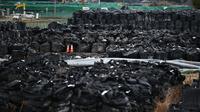 Foto ini diambil pada 29 Februari 2020 menunjukkan tanah permukaan yang terkontaminasi radiasi yang dikemas dalam tas hitam di sebuah lapangan di Tomioka, prefektur Fukushima di sebelah utara PLTN Daiichi Daiichi Fukushima yang rusak parah akibat gempa dan tsunami 2011. (AFP/Charly Triballeau)