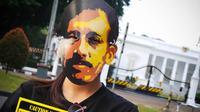 Jaringan Solidaritas Korban untuk Keadilan dan penggiat HAM mengenakan topeng Munir di depan Istana Negara, (4/9/14). (Liputan6.com/Faizal Fanani)