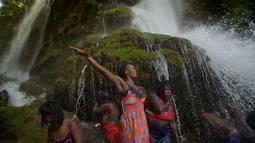 Sejumlah peziarah mandi di bawah air terjun di Saut d' Eau, Haiti (15/7). Mereka merupakan penganut Kristen Haiti yang masih percaya Voodoo. (AFP Photo/Hektor Retamal)