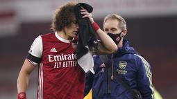 Bek Arsenal, David Luiz memegang handuk pada luka di kepalanya setelah terlibat benturan dengan Raul Jimenez dari Wolverhampton Wanderers pada pekan kesepuluh Liga Inggris di Emirates Stadium, London, Minggu (29/11/2020). Arsenal takluk 1-2 dari Wolverhampton Wanderers. (John Walton/Pool via AP)