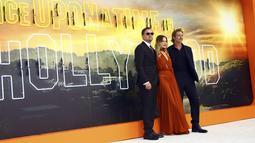 Aktris Margot Robbie berpose dengan Leonardo DiCaprio dan Brad Pitt saat menghadiri premier film Once Upon a Time In Hollywood di sebuah bioskop di London, Inggris (30/7/2019). (AP Photo/Joel C Ryan)