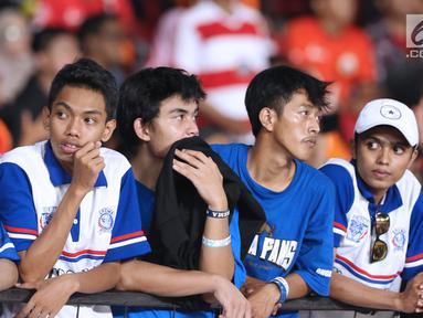 Suporter tim Singo Edan terlihat kecewa saat kekalahan Arema FC dari Persija pada lanjutan Go-Jek Liga 1 Indonesia 2018 bersama Bukalapak di Stadion GBK Jakarta, Sabtu (31/3). Arema FC kalah telak 1-3. (Liputan6.com/Helmi Fithriansyah)