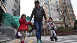 Gambar ini diambil pada 22 Desember 2015 menunjukkan seorang ayah dari Korea Selatan, Kim Jin-Sung (tengah) berjalan bersama putrinya Na-Eun dan Won-Woo pulang dari pusat penitipan anak di Seoul. (AFP PHOTO/JU)