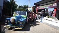 Warga menaiki odong-odong untuk menggunakan hak pilihnya di TPS Kampung Pilkada RW 03, Depok, Jawa Barat, Rabu (9/12). Di Kampung Pilkada RW3 disajikan hiburan dan bazar, agar warga berbondong-bondong datang ke TPS (Liputan6.com/Immanuel Antonius)
